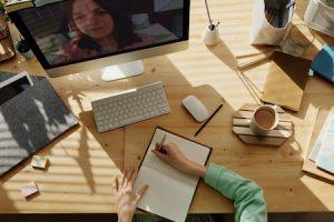 imagen mujer escribiendo mientras asiste a una videoconferencia